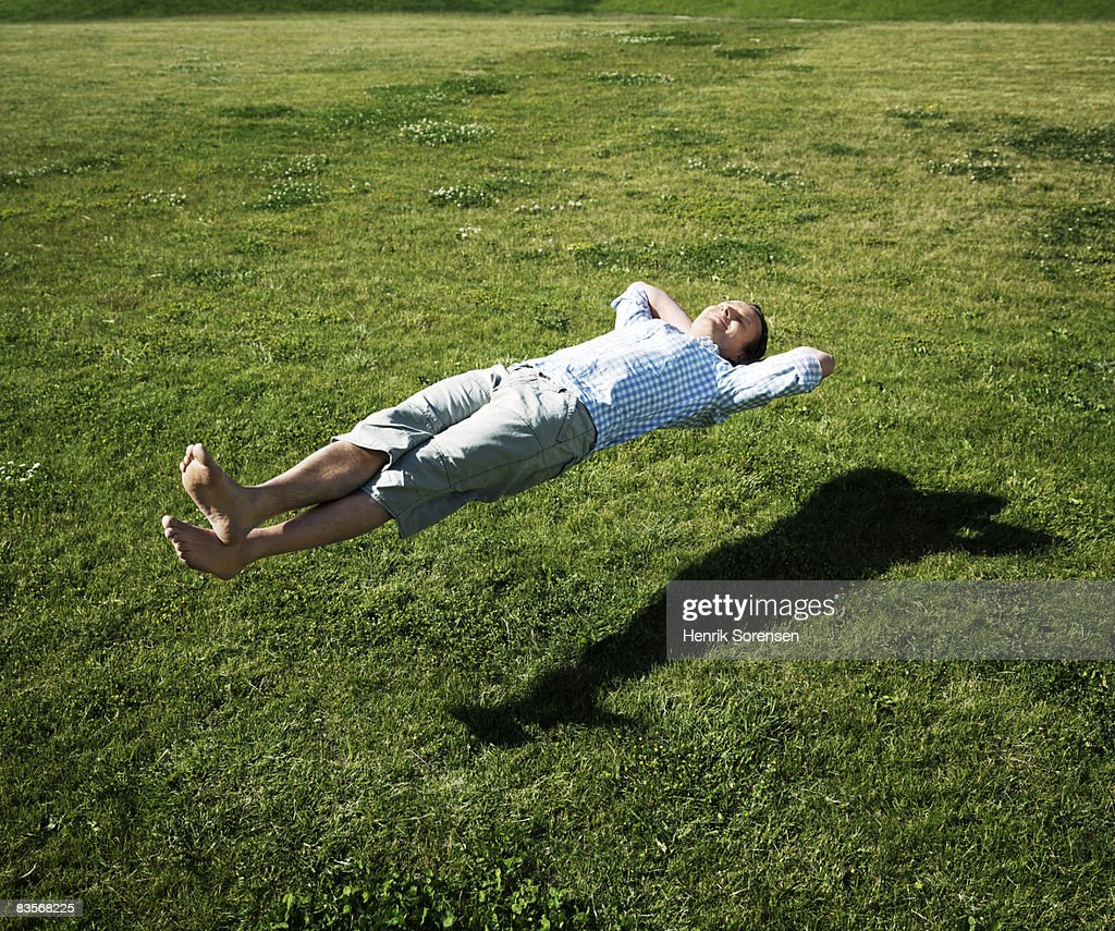 Man realxing floating above the grass