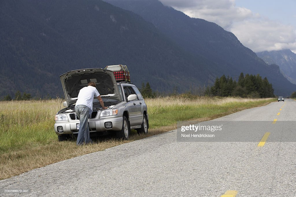 Man, rear view, checking engine of sports utility vehicle beside rural road