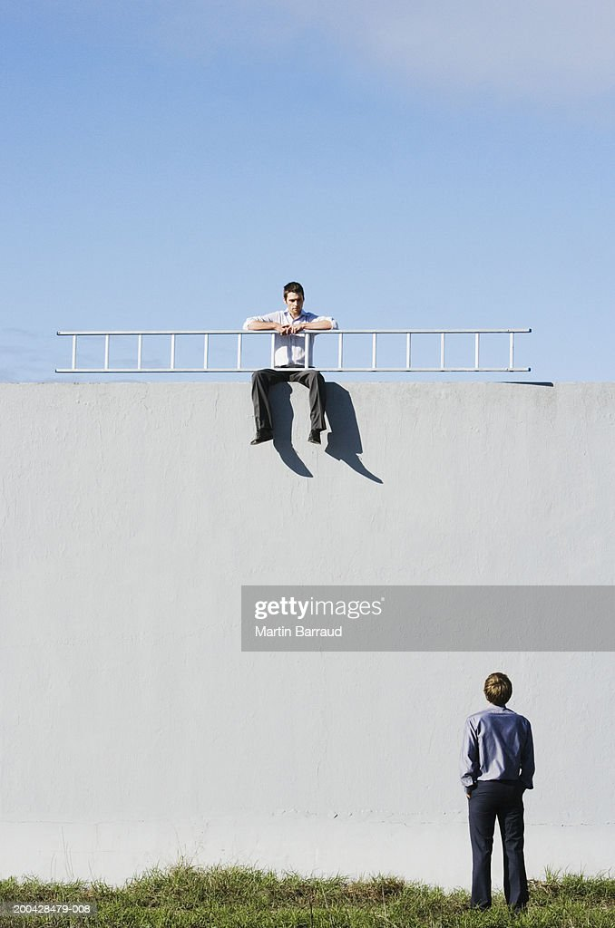 Man, rear view, looking up at man sitting on wall holding ladder : Stock Photo