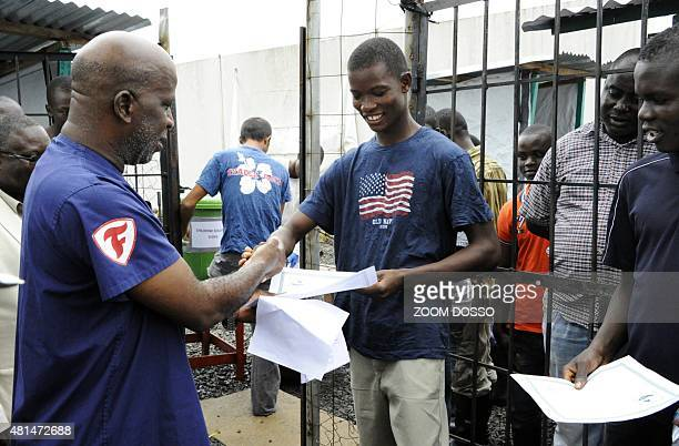 A man receives a certificate with a clean billofhealth from the Elwa clinic an ebola treatment center in Monrovia on July 20 2015 AFP PHOTO / ZOOM...