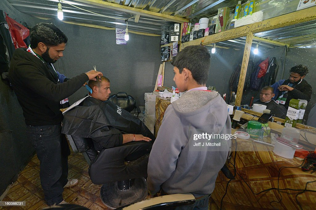 ZA'ATARI, JORDAN - JANUARY 30: A man receives a haircut in a barbers as Syrian refugees go about their daily business in the Za'atari refugee camp on January 30, 2013 in Za'atari, Jordan. Record numbers of refugees are fleeing the violence and bombings in Syria to cross the borders to safety in northern Jordan and overwhelming the Za'atari camp. The Jordanian government are appealing for help with the influx of refugees as they struggle to cope with the sheer numbers arriving in the country.