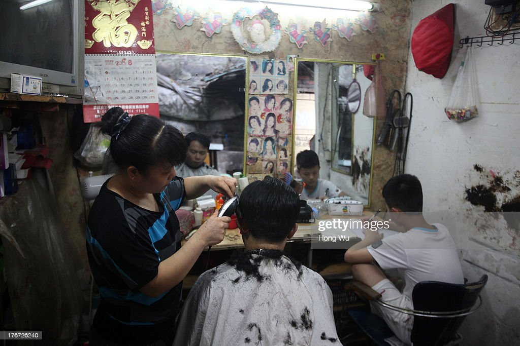 A man receives a haircut in a small barbershop on August 4, 2013 in Chongqing, China. Chongqing is a major city in southwest China and became the municipality was created on 14 March 1997. It known as a 'Mountain City' and 'River City' was constructed on the mountain and along the Yangtze River.