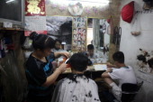 A man receives a haircut in a small barbershop on August 4 2013 in Chongqing China Chongqing is a major city in southwest China and became the...