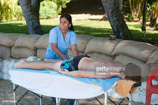 A man receives a massage on the beach at Playa Tamarindo in Costa Rica