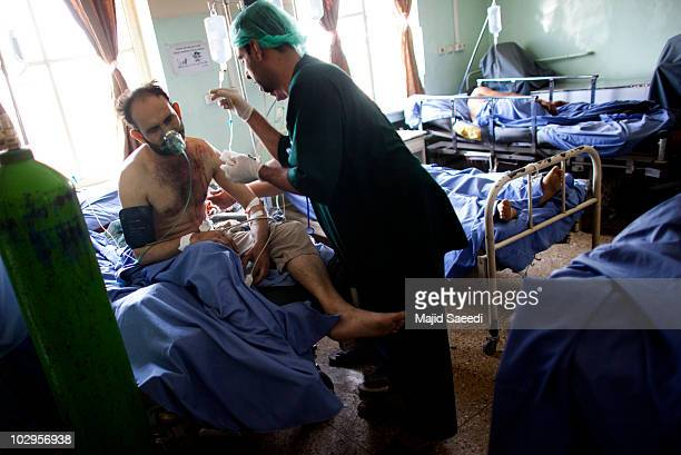 A man receives treatment from a doctor for injuries sustained during a suicide bomb attack in an Afghan hospital on July 18 2010 in Kabul Afghanistan...