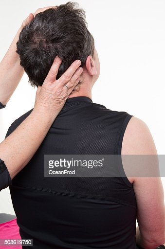 Man receiving neck massage in a medical office : Stock Photo
