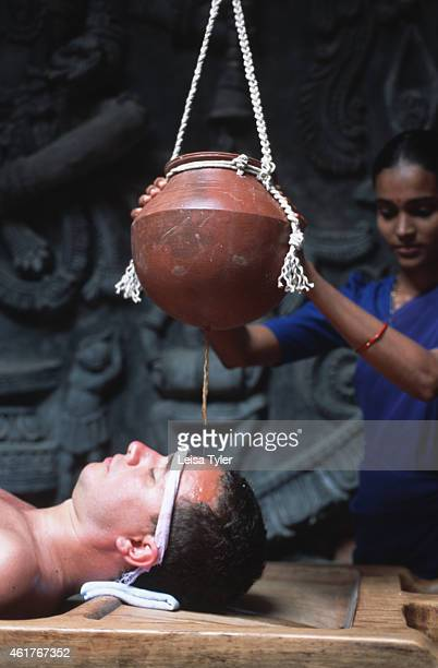A man receiving shirodhara a treatment from ayurveda where warm herbal oil is poured onto the head in a rhythmic fashion curing head and brain...
