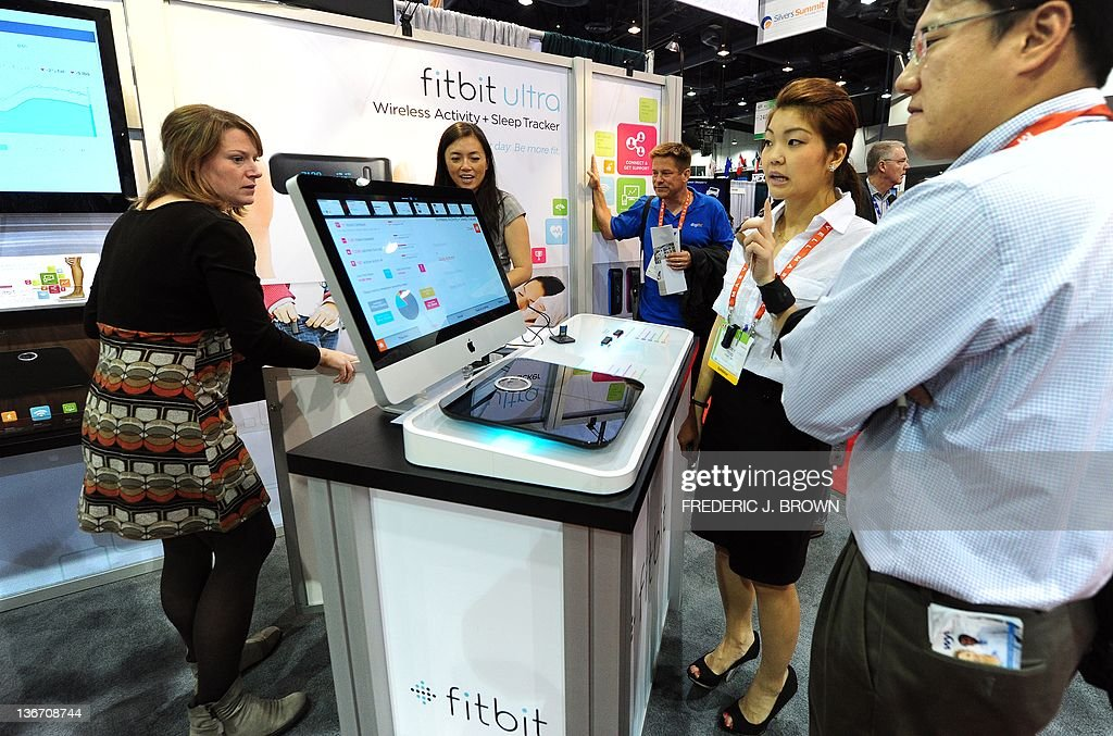 A man recieves an explanation on the Fitbit Aria Wi-Fi scale, which can tap into a home wireless network to upload information on one's health each time the scale is stepped on, displayed on the opening day of the International Consumer Electronics Show on January 10, 2012 in Las Vegas, Nevada. The show kicked off with a dazzling array of high-tech gadgetry including ultra-thin laptops, snazzy smartphones, iPad rivals and flat-screen and 3D TVs with a record 3,100 companies from around the world displaying their goods over a space equivalent to more than 35 football fields in the cavernous Las Vegas Convention Center for the four-day event. AFP PHOTO / Frederic J. BROWN