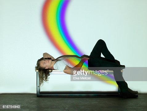 man reclined on bench with rainbow : Stock Photo