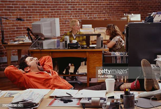 Man reclining and yawning in office