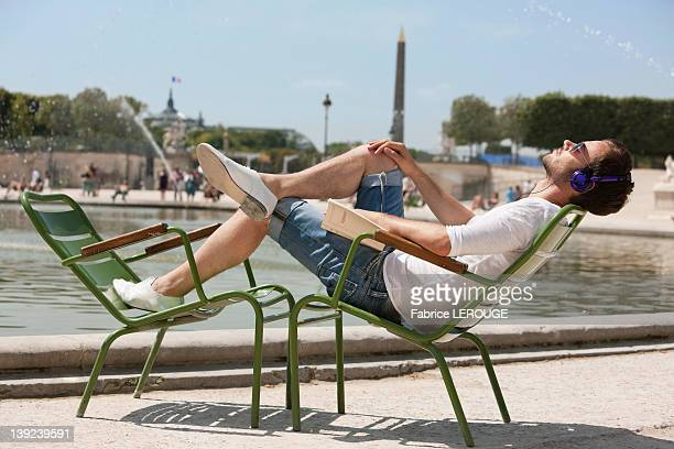 Man reclining in a chair and listening to music, Bassin octogonal, Jardin des Tuileries, Paris, Ile-de-France, France
