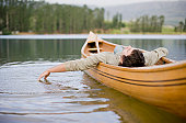 Man reclining in canoe on lake