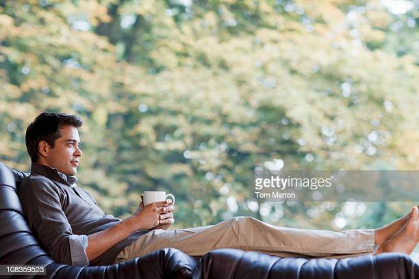 Man reclining in chair drinking coffee