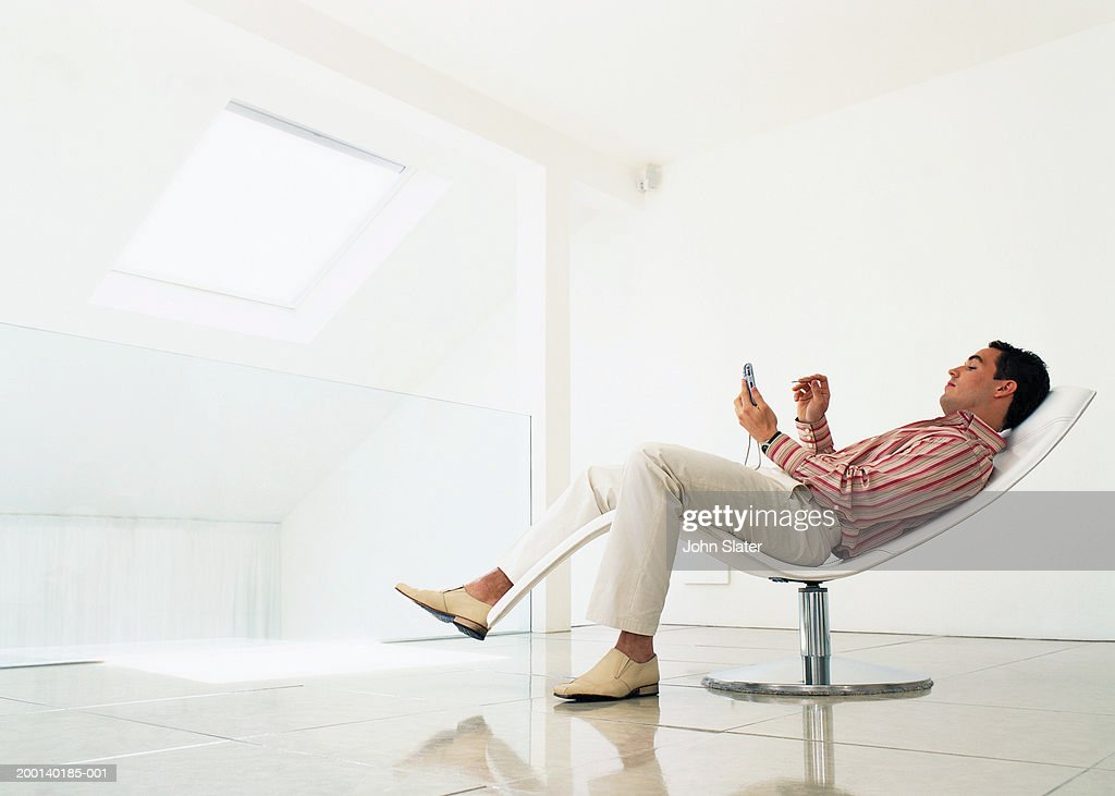 Man reclining on chair using electronic organiser, side view : Stock Photo