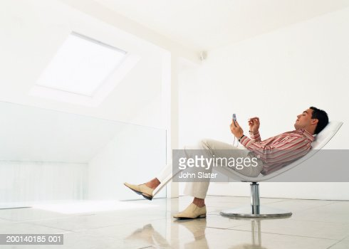 man reclining on chair using electronic organiser side view