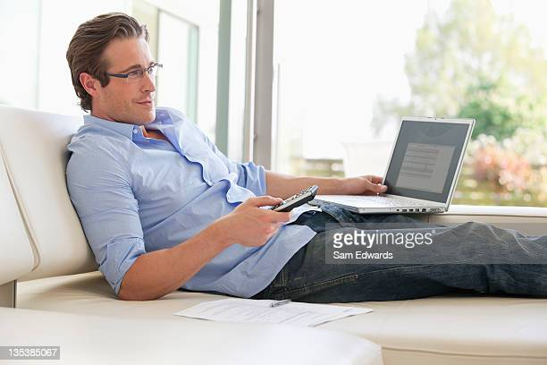 Man reclining on sofa using remote control and laptop