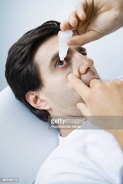 Man reclining, putting eyedrops in one eye
