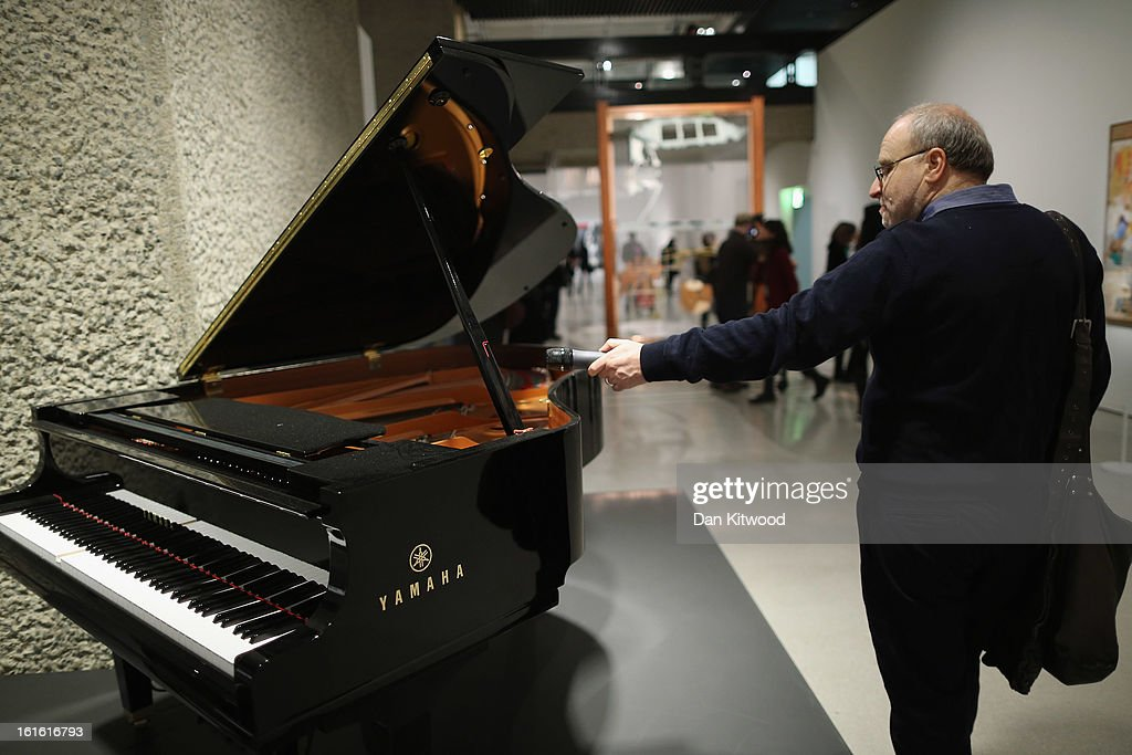 A man records a piece of music playing from a piano by composer John Cage during a press preview of 'The Bride and the Bachelors' exhibition at the Barbican Art Gallery on February 13, 2013 in London, England. The piece makes up a selection of works by artists and choreographers including Marcel Duchamp, Merce Cunningham, John Cage, Robert Rauschenberg and Jasper Johns, and runs at the Barbican Art Gallery until June 9, 2013.