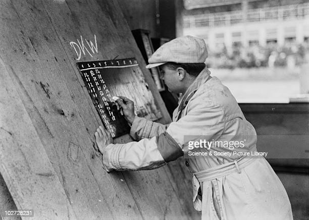 Man records numbers on blackboard beside car racing track Photograph by Zoltan Glass c1930 Man records numbers on blackboard beside car racing track...