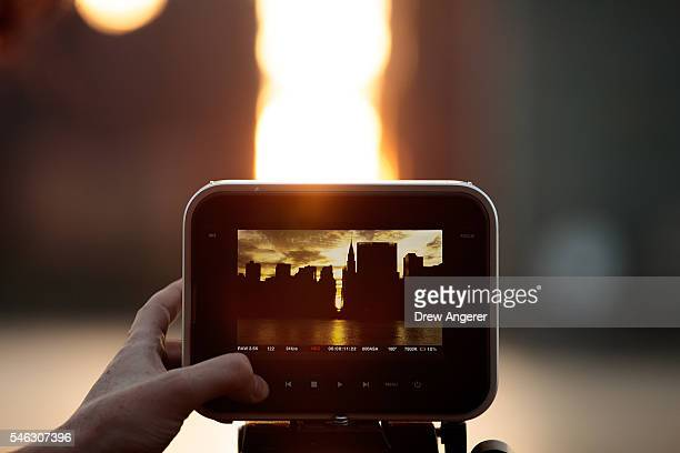A man records video of the 'Manhattanhenge' sunset from Hunters Point South Park July 11 2016 in the Queens borough of New York City 'Manhattanhenge'...