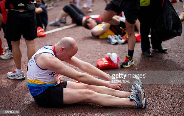 A man recovers after crossing the finish line of the 2012 London Marathon on April 22 2012 AFP PHOTO / LEON NEAL