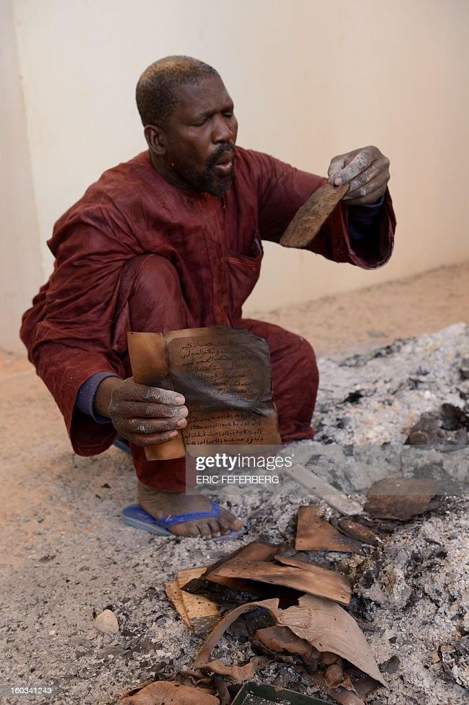 A man recovers burnt ancient manuscripts at the Ahmed Baba Centre for Documentation and Research in Timbuktu on January 29, 2013. French-led forces seized yesterday Mali's fabled desert city of Timbuktu in a lightning advance north as fleeing Islamists torched a building housing priceless ancient manuscripts. Mayor Ousmane confirmed the fire at the Ahmed Baba Centre for Documentation and Research which housed between 60,000 and 100,000 manuscripts, according to Mali's culture ministry. AFP PHOTO / ERIC FEFERBERG