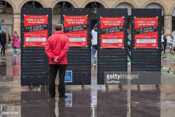 Man reds banners of the group 'les Morts de la Rue' on the Place du Palais Royal in Paris on March 21 in memory of 501 homeless people who died in...