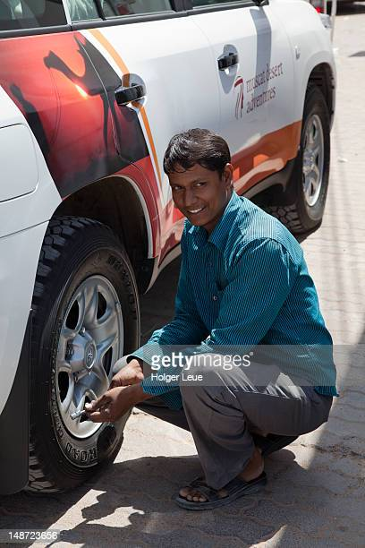 Man reducing tyre pressure on 4WD vehicle in preparation for a sand dune tour in Wahiba Sands desert.