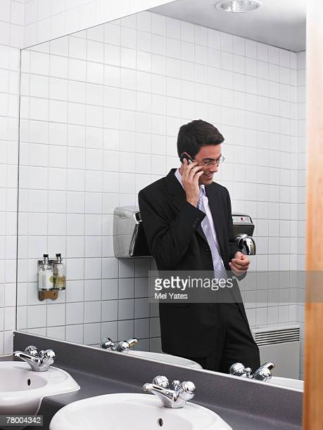 Man reflected in office washroom mirror using mobile phone