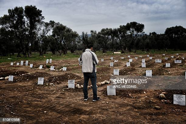 TOPSHOT A man reflects while standing in front of graves in Mytilene on February 17 at a graveyard for refugees and migrants who drowned in their...
