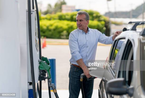 Man refueling his car at a gas station