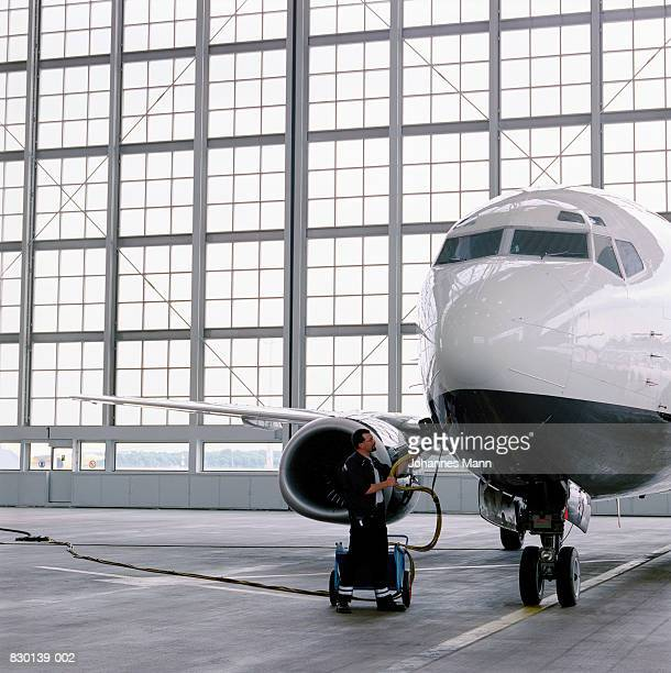 Man refuelling commercial aircraft in hangar