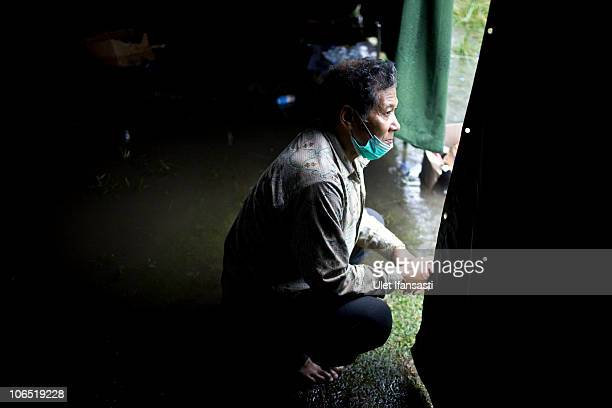 A man refugee waits in a flooded tent due to rain at a temporary evacuation centre set up as a result of the repeated eruptions of Mount Merapi in...