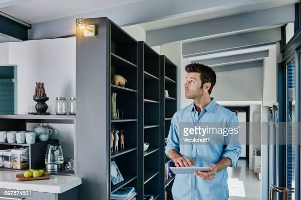 Man regulating lamp with digital tablet