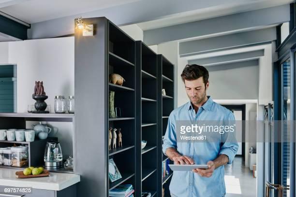 Man regulating light with his digital tablet
