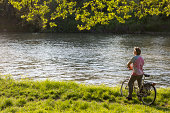 Man relaxes against bicycle at river's edge