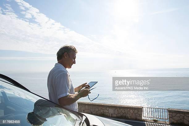 Man relaxes against car, using digital tablet
