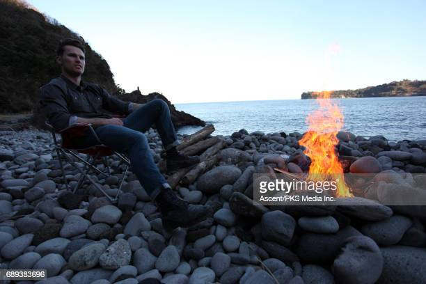 Man relaxes by fire after on rocky ocean beach
