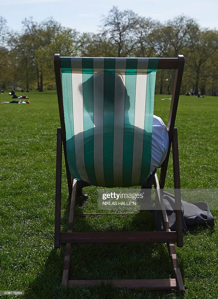 A man relaxes in a deck chair in the afternoon sunshine in Green Park, central London on May 4, 2016. / AFP / NIKLAS HALLE'N