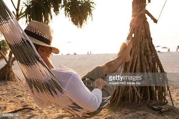 Man relaxes in hammock, sleeps under hat