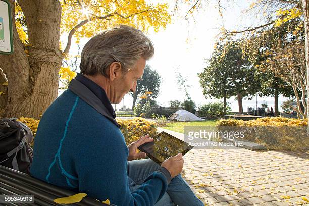 Man relaxes in park bench, uses digital tablet
