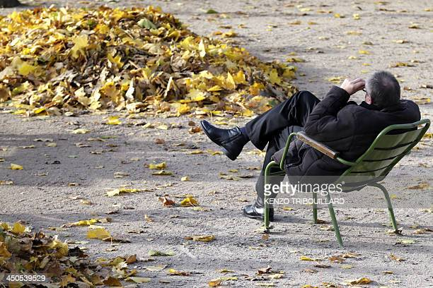 A man relaxes near a pile of fallen leaves on November 19 2013 in the Tuileries garden in Paris AFP PHOTO / KENZO TRIBOUILLARD