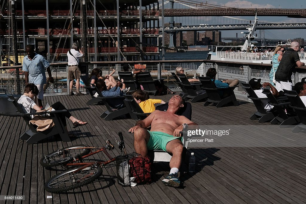 A man relaxes on a sun deck at South Street Seaport in lower Manhattan on a warm June evening on June 30, 2016 in New York City. New York City residents and thousands of tourists are preparing for the Fourth of July weekend which is expected to be warm and sunny.