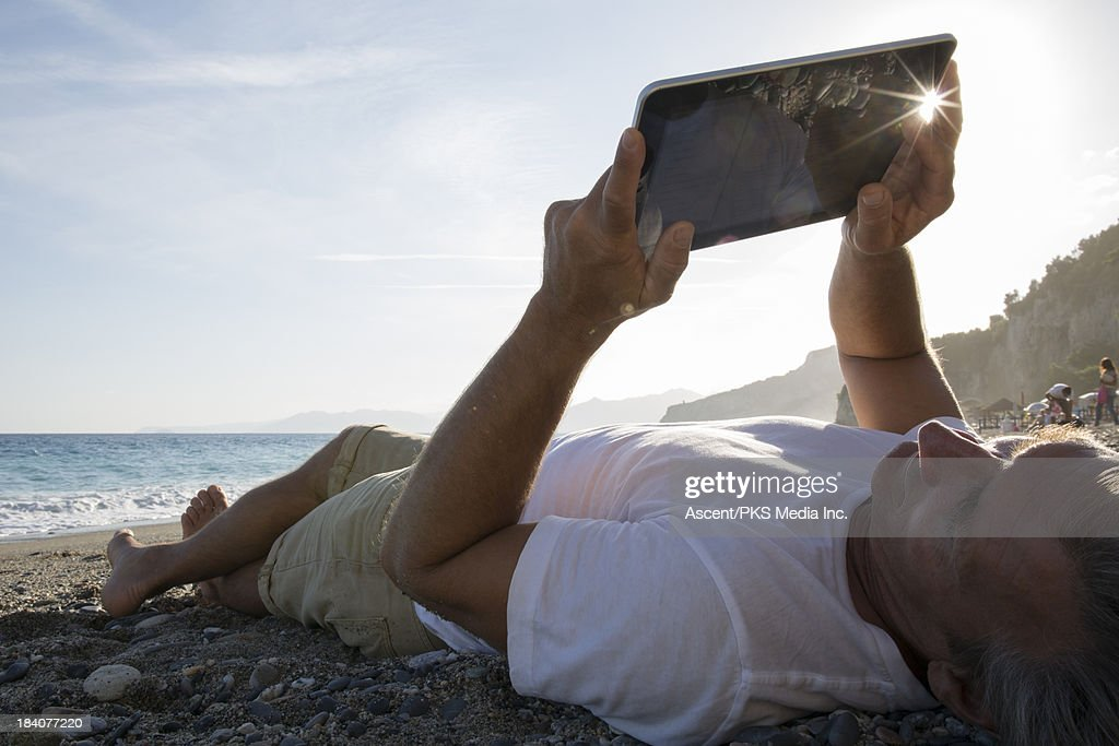 Man relaxes on beach, uses digital tablet