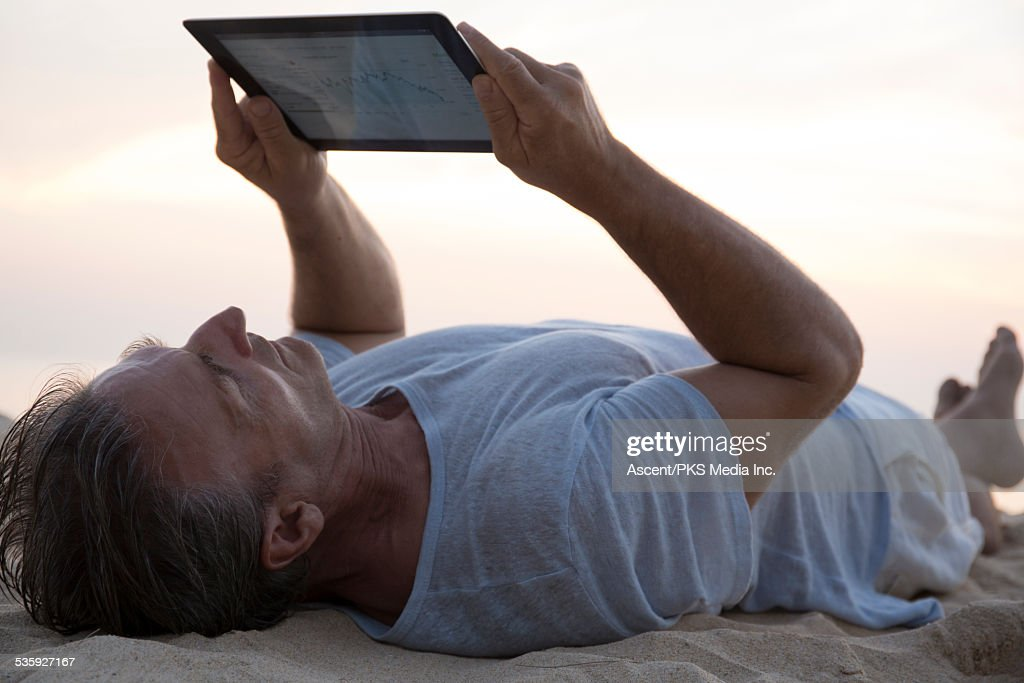 Man relaxes on beach, with stock tables on tablet : Stock Photo