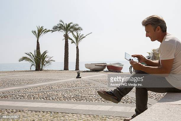 Man relaxes on bench, uses digital tablet, beach