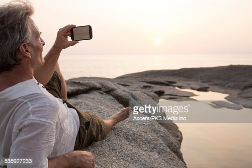 Man relaxes on rock above pond, takes pic of sea : Stock Photo