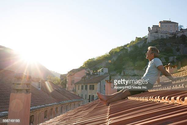 Man relaxes on tiled roof, looks across village