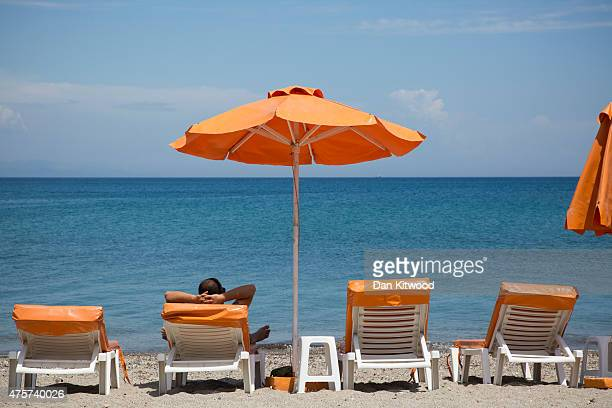 A man relaxes under parasols on the beach front on June 03 2015 in Kos Greece The Island has recently seen a drop in tourist numbers which has been...