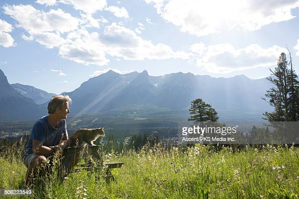 Man relaxes with cat in mountain meadow